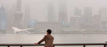 Shanghai, China - April 20, 2010: Air Pollution, high-rises shrouded in heavy smog,  air in City remained severely polluted, man standing on the Bund, and looks at the Pudong District. CBN's 15 trillion naira infrastructure fund set to launch in October CBN's 15 trillion naira infrastructure fund set to launch in October Iblog 360x160
